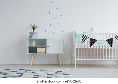 Cozy interior of kid's bedroom with a mint water drop stickers on the wall, a plant standing on a cupboard, and a small bed for a baby decorated with washi tape