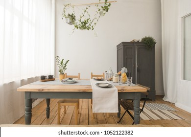 Cozy interior of kitchen with wooden table and cupboard and green plants in decor.