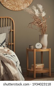 Cozy interior of stylish bedroom with design decoration, wooden bedside table, ceramic vessel, book, beautiful bed sheets, blanket ,pillows and personal accessories. Template.