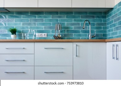 A cozy interior of a white kitchen with a blue tile