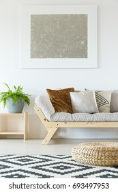 Cozy interior in white natural studio apartment with beige couch, wood, plants, rattan pouf, artwork and patterned rug