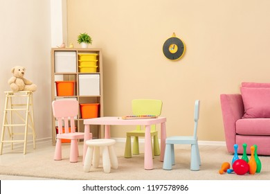 Cozy kids room interior with table, sofa and shelving unit