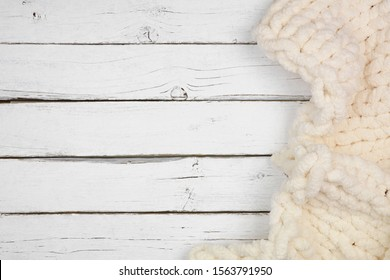 Cozy knitted thick wool blanket. Side border above view on a white wood background with copy space. Cream color.