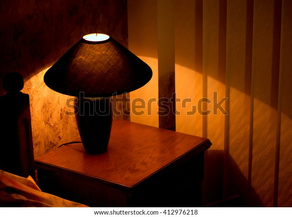 Cozy lamp on a night stand near a bed (shining in the darkness)