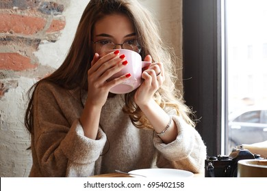 Cozy lifestyle shot of gorgeous European student girl wearing trendy glasses enjoying aroma and flavor of coffee while relaxing at coffee shop at daylight after morning lectures at university