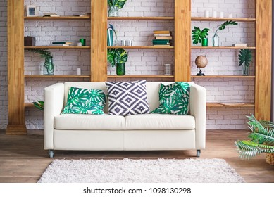 Cozy light room with plants, white sofa and stylish furniture in scandinavian style. Living room interior concept. Selective focus. Space for text.