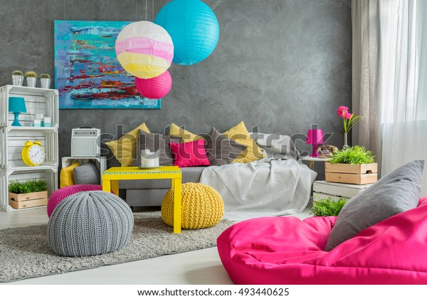 Cozy living room in grey with window, modern furniture and colorful details