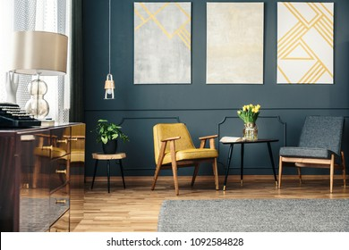 Cozy living room interior with armchairs, rug on the floor, flowers on the table, plant and paintings on the wall