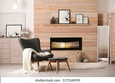 Cozy living room interior with comfortable furniture and decorative fireplace