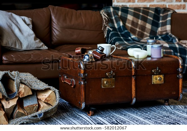 Cozy living room with sofa and plaid. Vintage photo camera and cup of coffee. Vintage style interior.