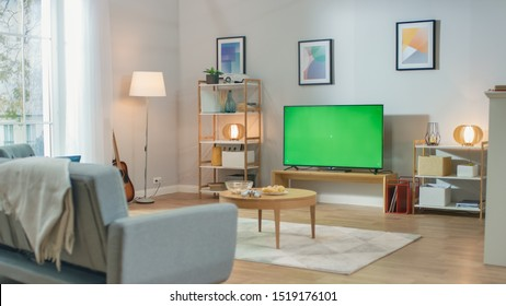 Cozy Living Room with Stylish Furniture and Design, Green Chroma Key TV in the Middle of the Room.