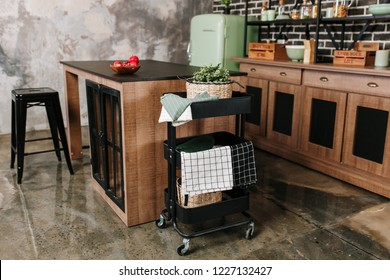Cozy loft kitchen with dinning table, chairs and metal storage racks on wheels - trolley.