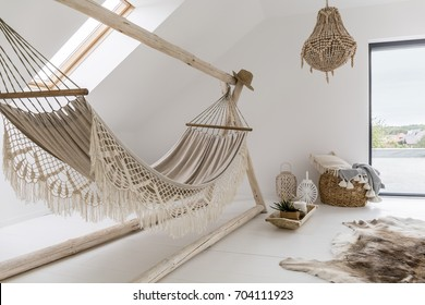 Cozy looking hammock in a stylish day room with a big chandelier