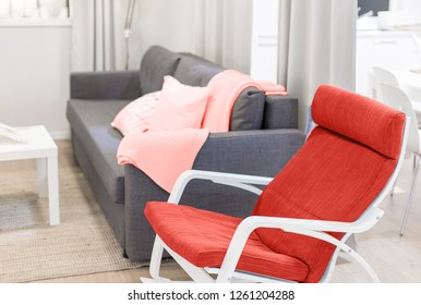 cozy minimalistic interior design in pastel colors in pink and gray. textile pillows, sofa and plaid. living coral