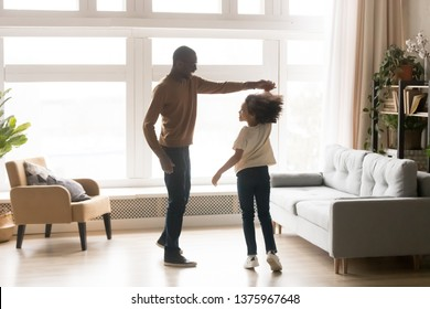 In cozy modern living room moving black father biracial schoolgirl bairn, loving dad hold daughter hand people dancing waltz, cheerful child swirling, active family enjoy time together at home concept