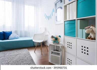 Cozy modern room designed for little boy. Grey carpet on wooden floor