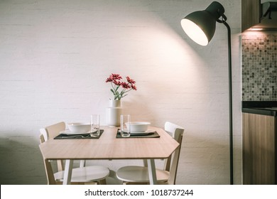Cozy and modern style dining room; Contemporary dining wooden table on which cutlery is setting with classic tall lamp's spotlight