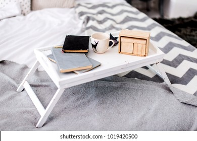 Cozy morning. Morning coffee and breakfast on a tray with books in a bed with a modern gray and white veil and pillows. An empty wooden calendar. Remote work at home, business and freelancing concept.