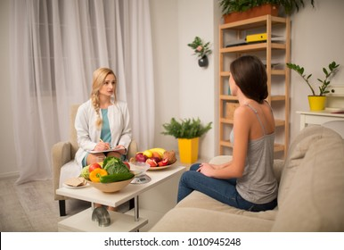 Cozy office of dietitian. Doctor and patient discussing dietary plan.