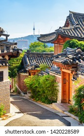 Cozy old narrow street and traditional Korean houses of Bukchon Hanok Village in Seoul, South Korea. Seoul Tower on Namsan Mountain is visible on blue sky background. Beautiful cityscape on sunny day.