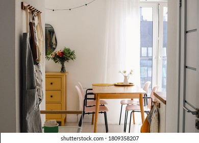 Cozy open dining room and living room interior with a window and a table with chairs. Scandinavian decor concept
