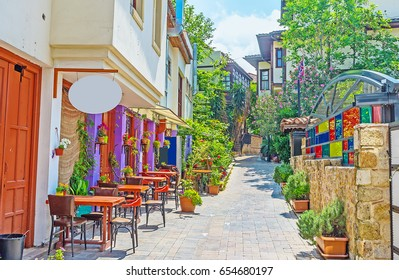 The cozy outdoor cafe in shady street of Kaleici neighborhood, decorated with flowers in pots, Antalya, Turkey.