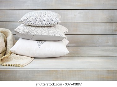 Cozy pillows and plaid on the light wooden background. Close up