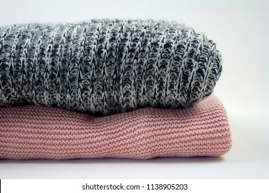 cozy pink and grey blankets in a pile stack