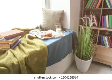 Cozy place for rest with books and tasty breakfast on windowsill