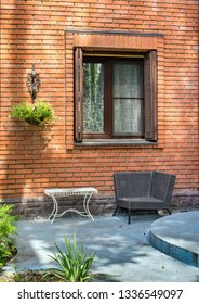 Cozy recreation area with wicker chair and metal white table in the yard of a country brick house