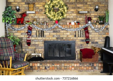 Cozy room with brick fireplace decorated for Christmas, rocking chair and piano, vintage stockings and lighted wreath hung.