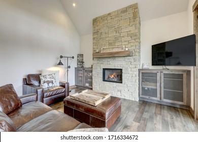 Confortable, rustique, nouveau salon de luxe, décoration intérieure avec grande cheminée en pierre et canapés en cuir,