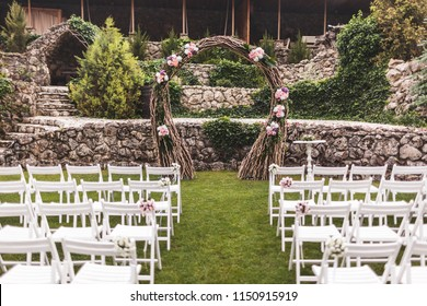 Cozy rustic wedding ceremony with flower arch and wooden white chairs in castle garden