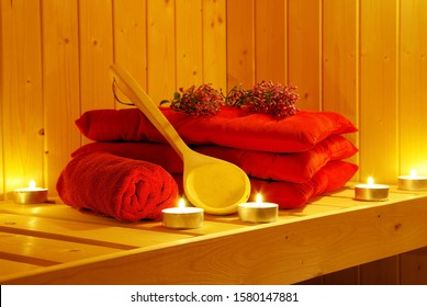 Cozy sauna room with sauna accessories red towels and pillows tea lights