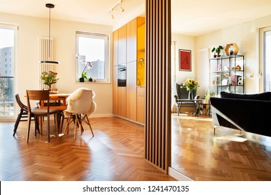 Cozy scandinavian open space with dining, living room and kitchen with design sofa and family table. Bright and sunny room with big windows and brown wooden parquet.
