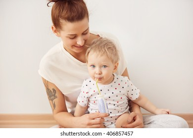 Cozy scene of happy Caucasian family spending time together, playing, hugging, smiling. Attractive young mother with her lovely kid on her laps, sitting on the floor at home against white background