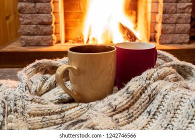 Cozy scene near fireplace with cups of hot tea and cozy warm scarf.