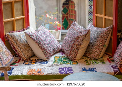 A cozy seating area near the window with colorful pillows with a wonderful view of the courtyard in Udaipur, Rajasthan, India. Close up