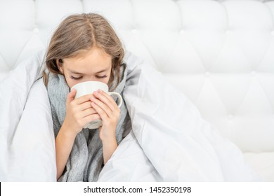 Cozy sick girl with flu sitting in bed and drinking tea at home. Empty space for text