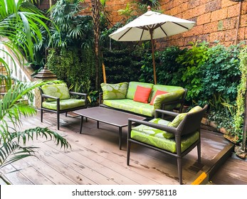 Cozy sofa, coffee table and umbrella in the garden. Bali style decoration.