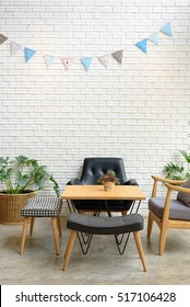 Cozy sofa corner in modern style. The chair is made with black leather and handmade wood, the table has small tree on top. The background is made with white brick in modern and industrial style.