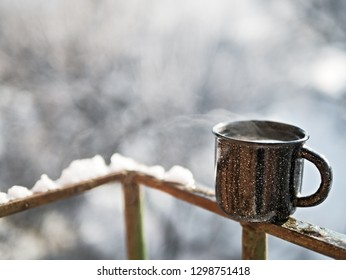 Cozy steaming cup with hot cocoa, tea or coffee. Mug winter morning or evening outdoors under snowfall. Winter and Christmas time concept.