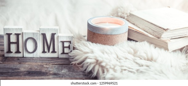 Cozy still life on a wooden background with details in the interior, and wooden letters with the inscription Home and a big beautiful candle, the concept of comfort and home style