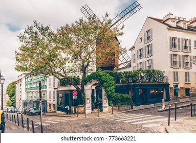 Cozy street with tables of cafe and old mill in quarter Montmartre in Paris, France. Architecture and landmarks of Paris. Postcard of Paris