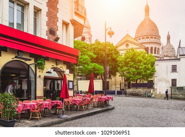 Cozy street with tables of cafe in quarter Montmartre in Paris, France. Architecture and landmarks of Paris. Postcard of Paris