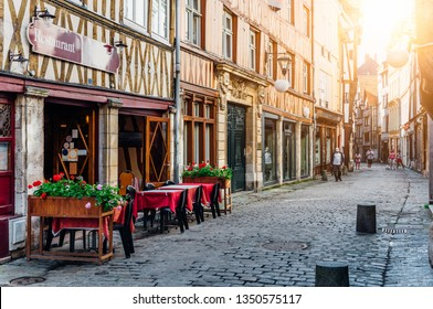 Cozy street with timber framing houses and tables of restaurant in Rouen, Normandy, France