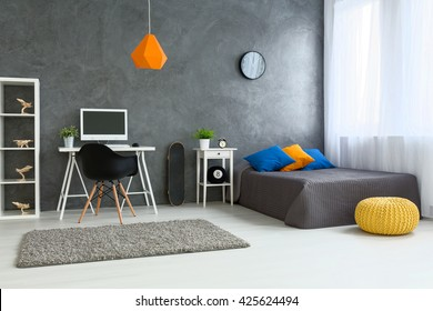 Cozy stylish bedroom designed for teenage boy. Grey walls and wooden floor. On the wall skate board and shelf with wooden models