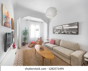 Cozy stylish bright living room with natural ratan carpet, sofa, wooden table, pictures and plants. Spacious modern interior in earthy colors