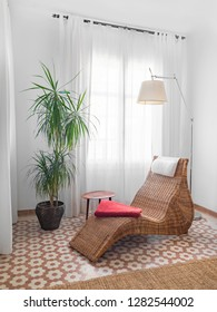 Cozy stylish natural fiber seat in a bright living room with wooden table, pictures and plants. Bohemian modern interior in earthy colors