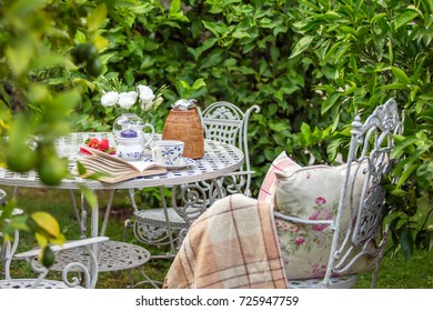 Cozy tea party at garden with book, teapot, candle, flowers, blanket. Beautiful metal lacy chairs and table. Nobody